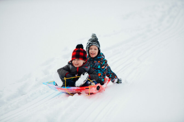 Two children sledding in Waterford MI